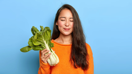 Indoor shot of delighted young woman returns from grocers shop, holds fresh green bok choy, keeps to healthy diet, wears orange jumper, isolated over blue background. Vegetables, vegetarian, calories