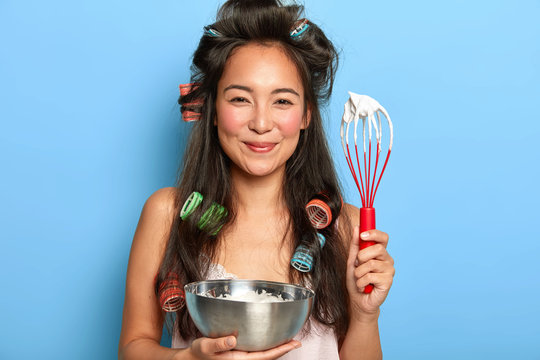 Photo of satisfied brunette woman whisks sour cream in bowl, wears hair curlers, dressed in nightdress, prepares something tasty for her family, poses against blue wall. Its time for cooking