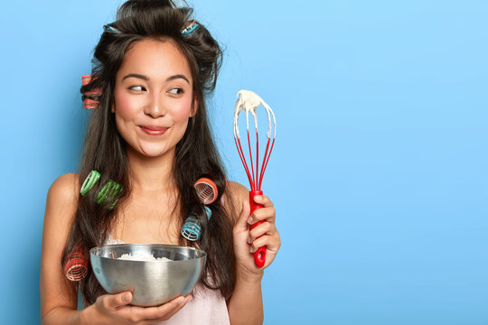 Korean housewife with hair curlers, busy cooking and preparing for birthday party, whisps cream with hand whisk, holds steel bowl dressed in domestic clothes has happy expression isolated on blue wall