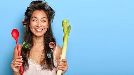Positive young Korean woman with gentle smile, holds red spoon and green leek, busy preparing healthy breakfast, keeps to diet for being fit, wears curlers and nightgown, isolated over blue wall