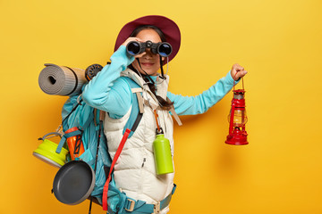 Obraz Horizontal shot of curious female backpacker explores tourist destination, uses binoculars, dressed in active wear, holds kerosene lamp carries travelling items with rucksack isolated over yellow wall - fototapety do salonu
