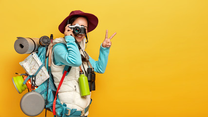 Photo of active female model makes shots on retro camera, shows peace gesture, dressed in casual clothes, carries rucksack, thermos and binoculars, has journey in wild place, isolated on yellow