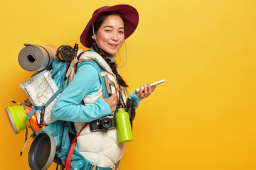 Photo of Asian lady with pleased expression, tries to find route with online navigation map, holds mobile phone, wears hat, casual clothes, carries rucksack, flask, binoculars, isolated on yellow wall
