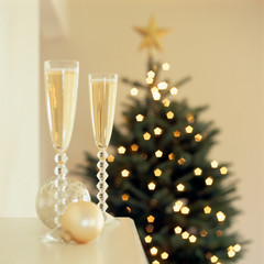 Glasses of sparkling wine Champagne on living room mantel with Christmas tree in background. Elegant, fancy living room holiday home interiors. Selective focus on one champagne glass.