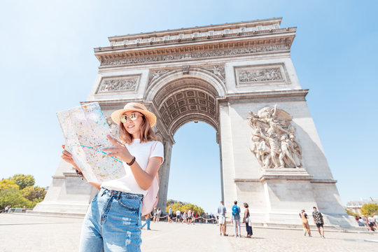 Happy Asian tourist girl enjoys the view of the majestic and famous Arc de Triomphe or Triumphal arch. Solo Travel and voyage to Paris and France