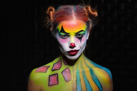 Sexy young woman with a face painting clown.