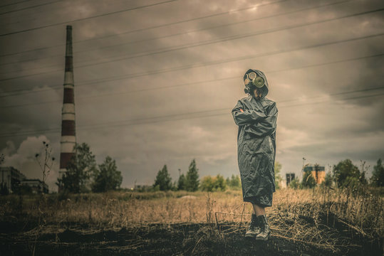Woman in gas mask is standing on a smoking chimney background.