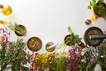 top view of mortars and pestles with herbal blends near flowers on white background
