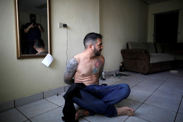 """A police officer takes a picture of a suspect in a seized MS-13 gang usurped house during a """"Casa Segura"""" (Safe House) operation at Jardines de San Bartolo neighborhood, in Ilopango"""