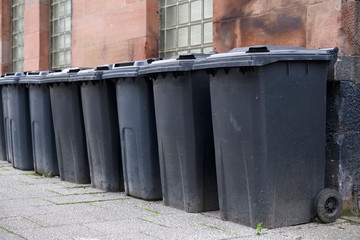 Black wheelie bins in a row on street with house numbers printed on front waiting for bin men to collect