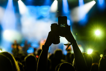 People taking photographs with smart phone during a public music concert with can of beer in hand