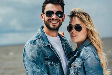 Fotomurales - attractive woman and handsome man in denim jackets looking at camera