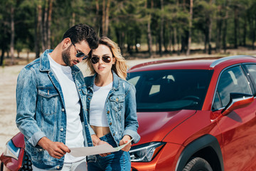 Fotomurales - attractive woman and handsome man in jackets looking at map