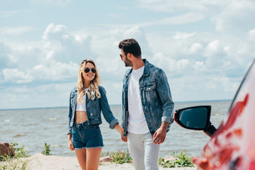 Fotomurales - attractive woman and handsome man in denim jackets holding hands outside