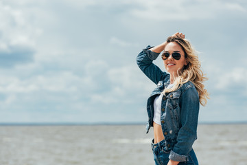 Fotomurales - blonde and attractive woman in denim jacket and sunglasses looking away