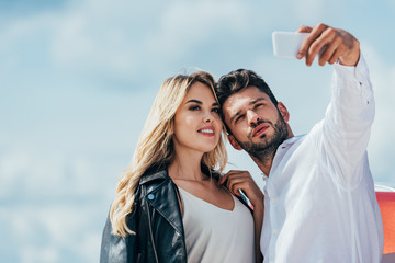 Fotomurales - attractive woman and handsome man smiling and taking selfie