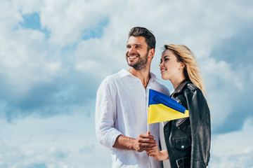 Fotomurales - attractive woman and handsome man holding ukrainian flag outside