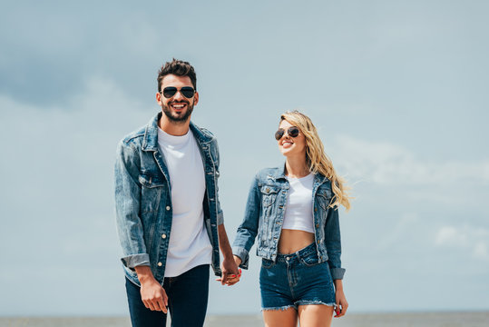 attractive woman and handsome man in denim jackets smiling and holding hands outside