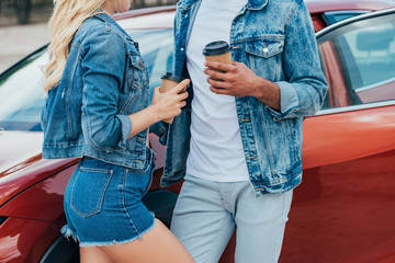Fotomurales - cropped view of woman and man in denim jackets holding paper cups