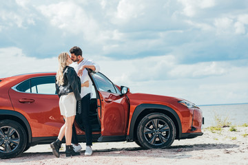 Fotomurales - attractive woman and handsome man kissing and hugging near car