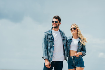 Fotomurales - attractive woman and handsome man in denim jackets smiling and hugging outside