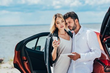 Fotomurales - attractive woman using smartphone and handsome man holding digital tablet