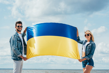 Fotomurales - attractive woman and handsome man smiling and holding ukrainian flag