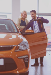 Dealer with woman stands near a new car in the showroom