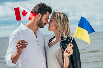 Fotomurales - attractive woman and handsome man holding canadian and ukrainian flags