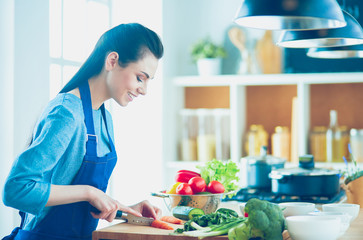 Young woman cutting vegetables in kitchen at home