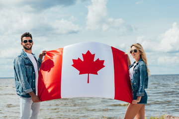 Fotomurales - attractive woman and handsome man smiling and holding canadian flag