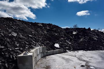 Pile of crushed reclaimed black road asphalt for reprocessing
