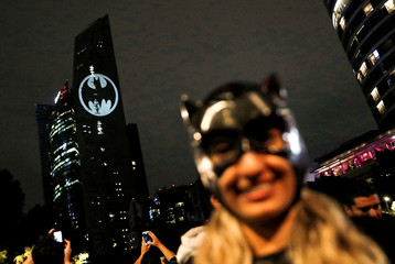 A Bat-Signal is projected onto a building at night as Batman fans celebrate the 80th anniversary of the first appearance of the DC Comics superhero, in Mexico City