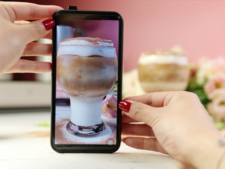 Female hands holding her mobile phone to take photos of coffee and milky drink in glass with pink background.