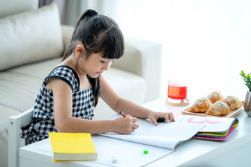 Asian preschool student do homework by reawing by a color