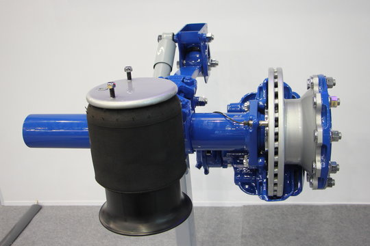 New truck semi trailer axle with air suspension and disk brake hub close up, heavy vehicle maintenance service