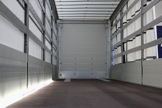 New truck empty semi trailer with clean floor, inside rear view close-up, lorry transportation logistics business