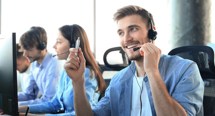 Portrait of call center worker accompanied by his team. Smiling customer support operator at work. Fototapete