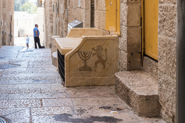 Bench with a picture of a Menorah and a lion in a quiet street of the Old City in Jerusalem, Israel