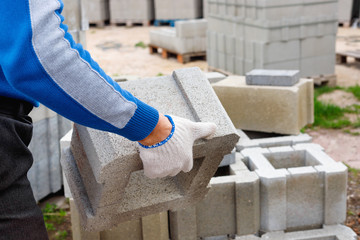 Worker loads cinder blocks  from cement slurry for construction