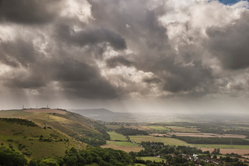 Poster Grijs Stunning Summer landscape image of escarpment with dramatic storm clouds and sun beams streaming down