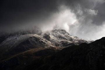 Stunning moody dramatic Winter landscape image of snowcapped Tryfan mountain in Snowdonia with stormy weather brooding overhead