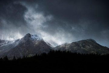 Stunning moody dramatic Winter landscape image of snowcapped Y Garn mountain in Snowdonia