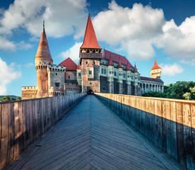 Amazing morning view of Hunyad Castle / Corvin's Castle. Great summer cityscape of Hunedoara town, Transylvania, Romania, Europe. Romanian castle landmarks. Traveling concept background.