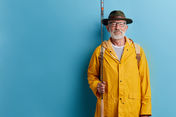 bearded old man in glasses going fishing, close up photo. isolated blue background, studio shot. copy space hobby, interest