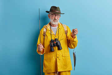 depressed old man is crying . he couldn't catch many fish, close up photo. isolated blue background, studio shot