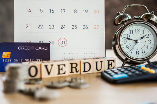 overdue bills concept with deadline calendar remind note,coins,credit card,calculator on table