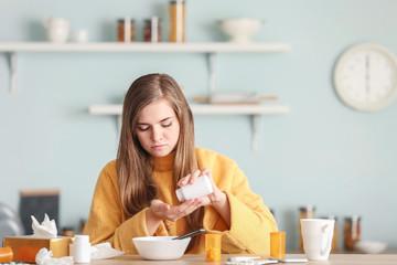 Sick woman taking medicine at home