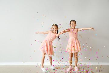 Portrait of happy twin girls with falling confetti near light wall
