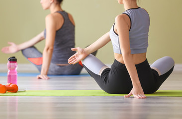 Young women practicing yoga in gym Fototapete